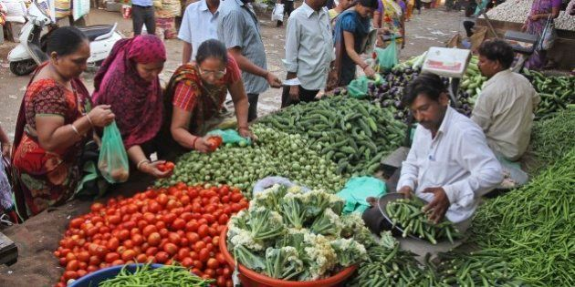 Indians buy vegetables at a market in Ahmadabad, India, Tuesday, Oct. 14, 2014. India's benchmark inflation...