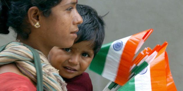 BANGALORE, INDIA: An Indian woman carries a small child as they sell tri-colour national flags at a traffic...