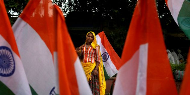 A woman laborer sells Indian flags outside the venue of an anti-corruption protest ahead of Indian Independence...