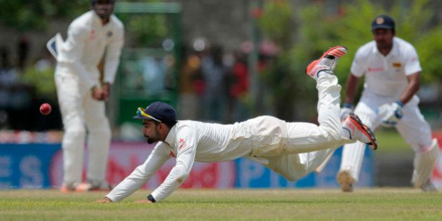 India's Virat Kohli dives to field a ball during the third day of the first cricket test match between...