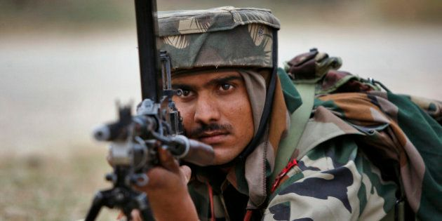 An Indian Army soldier takes position during an encounter with armed suspected militants at Pindi Khattar...