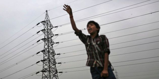 An Indian boy gestures as he stands near high tension electricity tower on a roadside in New Delhi, India,...