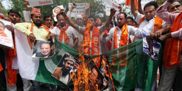 Hindu right-wing Shiv Sena activists burn a Pakistani flag along with posters of Pakistani Prime Minister...