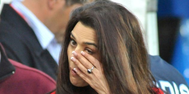Bollywood star Preity Zinta wipes a tear from her eye after hearing that two of IPL Punjab Kings players...