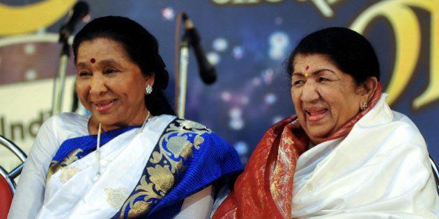 Indian Hindi and Marathi language Bollywood playback singer Lata Mangeshkar (R) sits alongside her sister...
