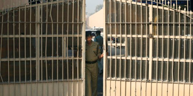 FILE- In this March 11, 2013 file photo, an Indian police officer prepares to close one of the gates...