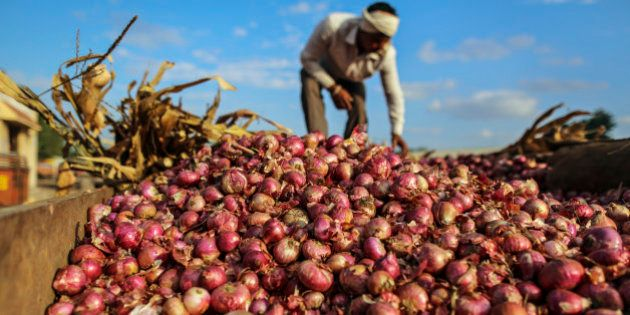 A farmer arranges onions in a tractor trailer at the Agriculture Produce Market Committee (APMC) wholesale...