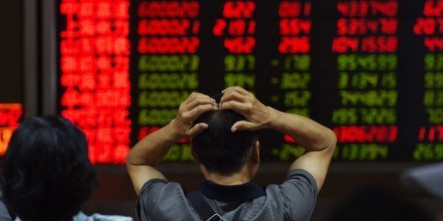 An investor looks at screens showing stock market movements at a securities company in Beijing on July...