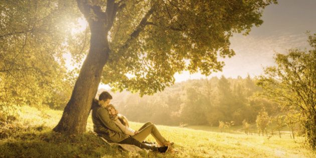 Loving couple under a big tree in the park in
