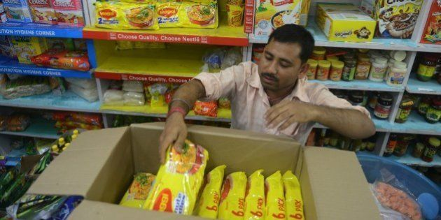 An Indian shopkeeper removes packets of Nestle 'Maggi' instant noodles from the shelves in his shop in...