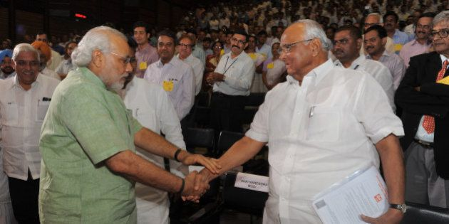 Gujarat state Chief Minister Narendra Modi (L) and Indian Union Agriculture Minister Sharad Pawar greet...