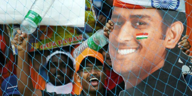 Kochi, INDIA: Indian supporters wave a cut out of player Mahendra Singh Dhoni during the fourth One-Day...