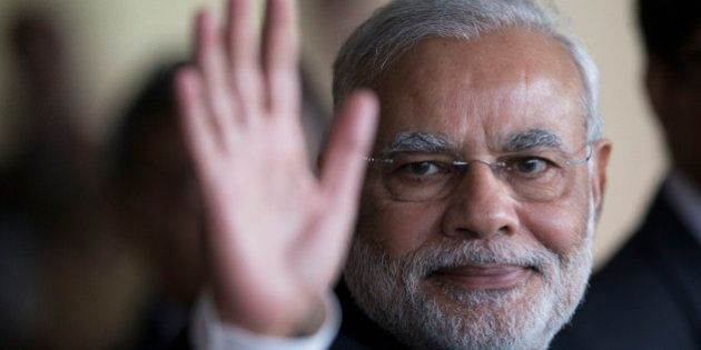 India's Prime Minister Narendra Modi waves to photographers as he leaves the Itamaraty Palace after attending...