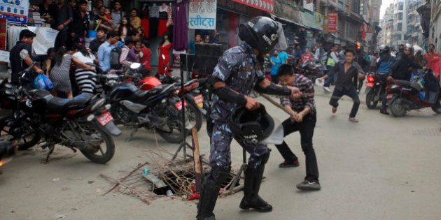 Nepalese protesters clash with a policeman during a torch rally in Kathmandu, Nepal, Saturday, Aug. 15,...