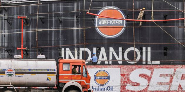 Workers perform maintenance work on Indian Oil Corp. tanks at Cochin Port in Cochin, India, on Friday,...