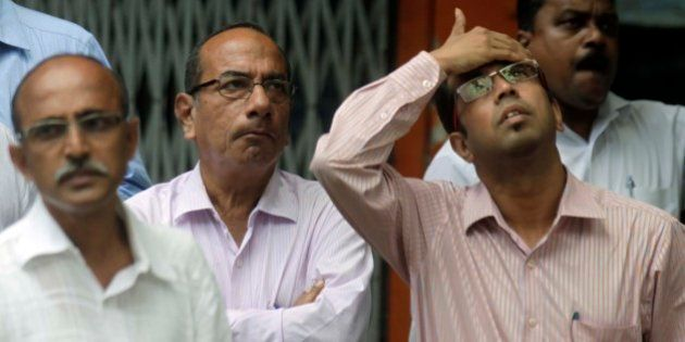 MUMBAI, INDIA - AUGUST 24: Anxious onlookers watch share prices on a screen outside the Bombay Stock...