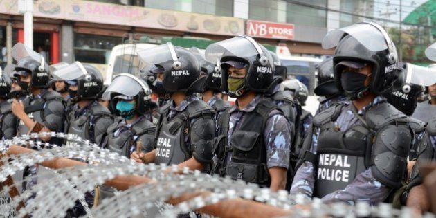Nepalese riot police stand guard near the Constitutional Assembly building during a protest by Nepalese...