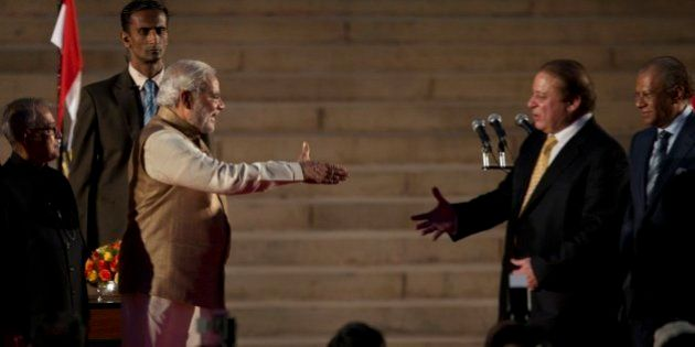 India's new prime minister Narendra Modi, left, prepares to shake hands with his Pakistani counterpart...