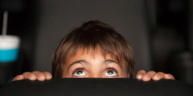 Boy peeking over top of seat during horror movie in