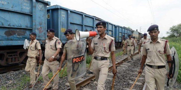 Indian police patrol railway tracks damaged by rioters on the outskirts of Ahmedabad on August 26, 2015....