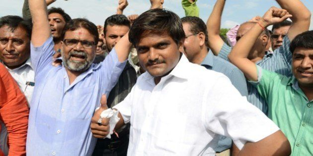 Hardik Patel (C), an organiser of the Patidar community, gathers with group members for a rally demanding...