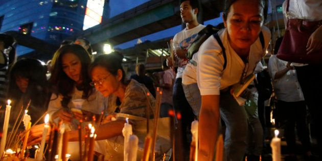 Thai people place lighted candles at the Erawan Shrine for the victims an explosion in Bangkok, Thailand,...