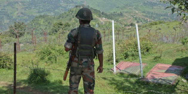 An Indian army soldier guards near fencing on the line of control near Balakot sector in Poonch, Jammu...