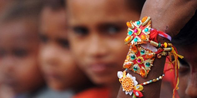 An Indian street child looks at his rakhi tied to his wrist by a member of a voluntary organisation in...