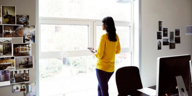 Female office worker looking out of a