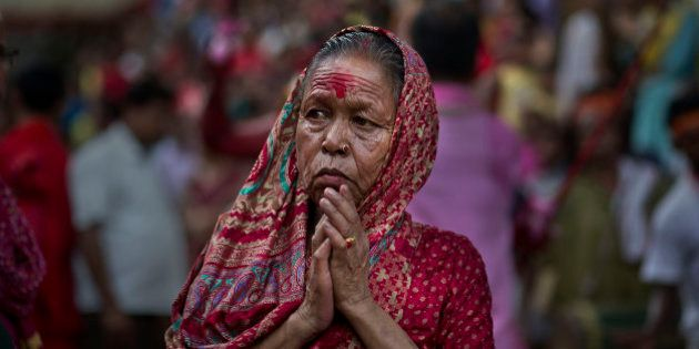 An Indian devotee offers prayers as she watches a priest carry a goat for sacrifice during the Deodhani...