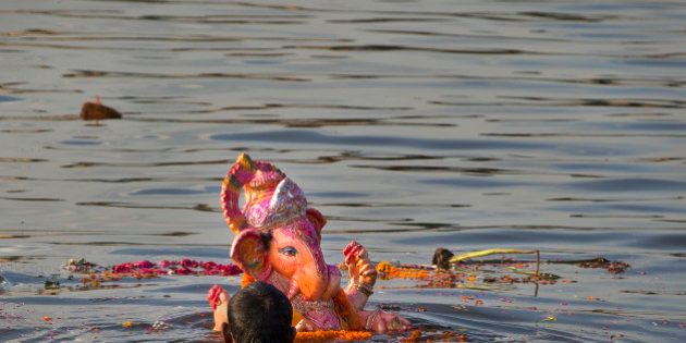 An Indian Hindu devotee immerses an idol of the elephant-headed Hindu God Ganesh into the river Yamuna,...