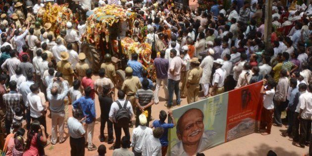 Indian mourners follow the funeral procession for scholar M.M. Kalburgi as he is taken to be buried at...