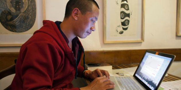 Jamyang Palden, a 30-year-old Tibetan Buddhist monk uses his laptop to access his email at a cafe with...