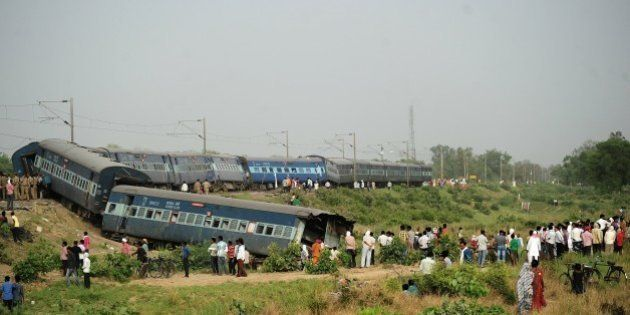Indian bystanders look at the coaches of the derailed Muri Express train near Sirathu some 65kms from...