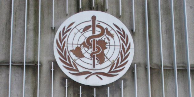 In this photo taken Wednesday, March 11, 2015, a man walks past the logo of the World Health Organization...