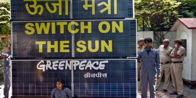 Indian policemen look on as Greenpeace activists chained to a bank of solar panels block the entry to...