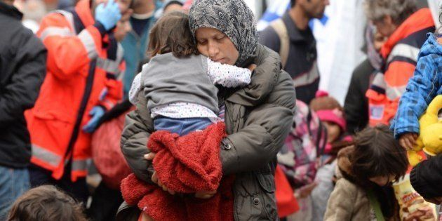 Migrant mother with a child waits for a first medical check after their arrival at the main railway station...