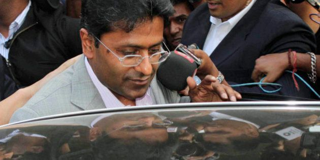 Indian Premier League (IPL) Chairman Lalit Modi prepares to enter a car after his arrival at the airport...