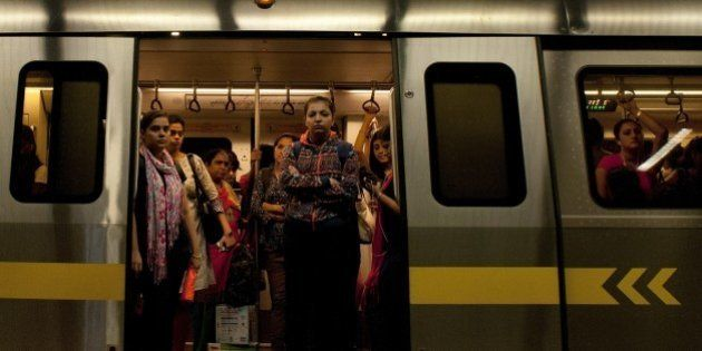 Indian women are framed in the doorway as they travel in the carriage reserved for women on the metro...