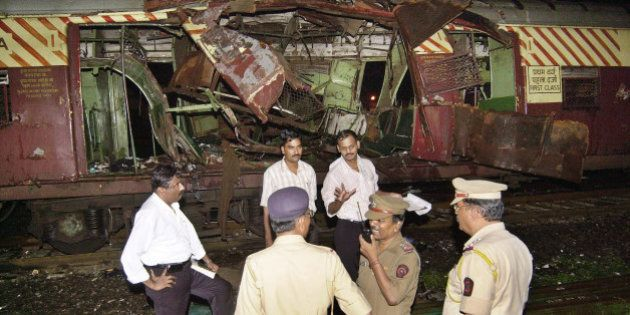 Police investigate near a train destroyed by a bomb blast at Mahim railway station in Mumbai, India,...