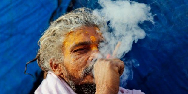 A Sadhu, or Hindu holy man, smokes marijuana to stay warm at Sangam, the confluence of rivers Ganges,...