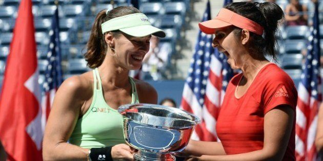 Sania Mirza (R) of India and her teammate Martina Hingis of Switzerland celebrate with their trophy after...