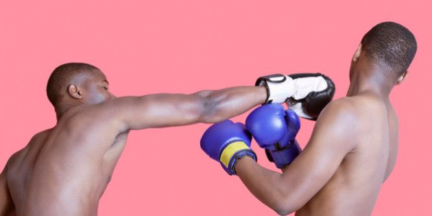 African American boxer punching opponent over pink