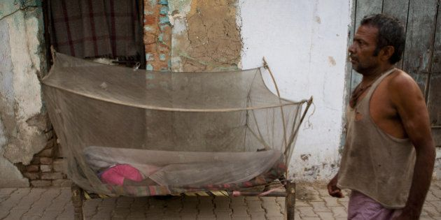 An Indian labourer walks past a women sleeping under a mosquito net in New Delhi early June 4, 2012....