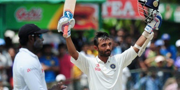 Indian cricketer Ajinkya Rahane raises his bat and helmet in celebration after scoring a century (100...