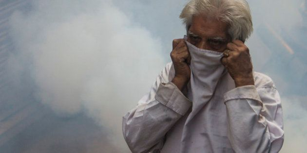 An Indian pedestrian protects his face as he is engulfed in a cloud of pesticide during a dengue prevention...
