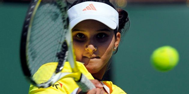 Sania Mirza of India, returns a shot to Mariya Koryttseva of Ukraine, during a first round match at the...