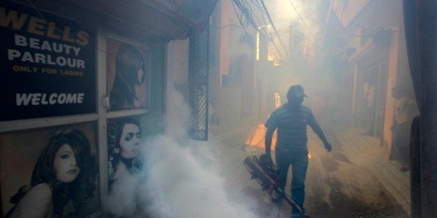 A Delhi municipal worker fumigate a residential area to prevent mosquitos from breeding in New Delhi,...