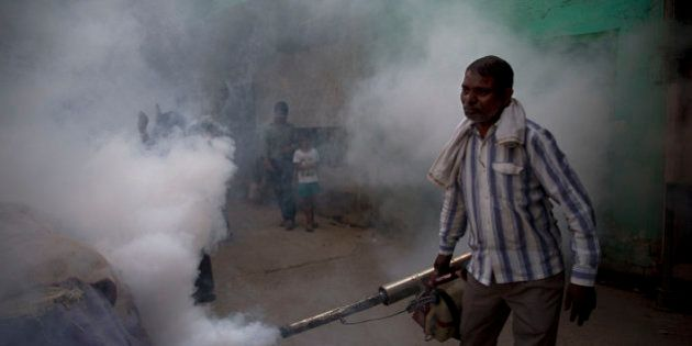 A municipal worker fumigates a residential area to prevent mosquitoes from breeding in New Delhi, India,...