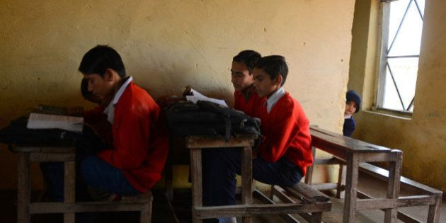 Schoolchildren sit in a classroom at a school near the India-Pakistan border in Gharana, some 35 kms...